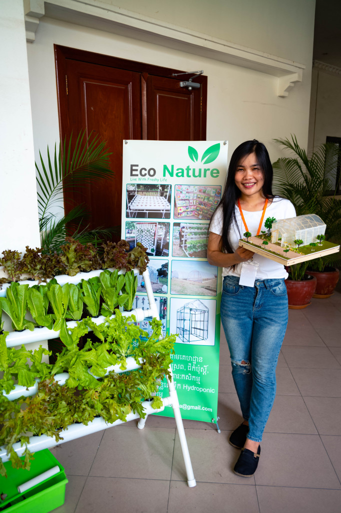 Dalen Kong posing with a model of her net house and hydroponics.